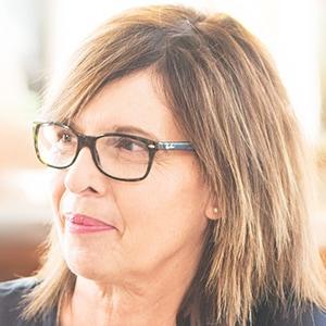 Mitarbeiterin mittleren Alters, hellbraunen Haaren und dunkler Brille