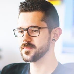 junger Mitarbeiter, dunkle Haare, schwarze grosse Brille, drei-Tage-Bart